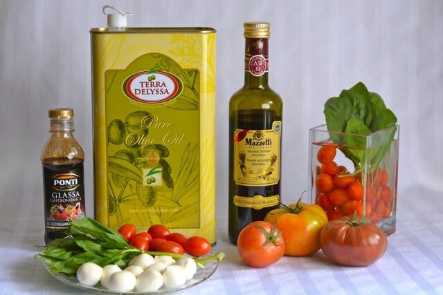 A bottle of Balsamic Glaze vs Balsamic Vinegar with fresh tomatoes, basil, bocconcini and olive oil.