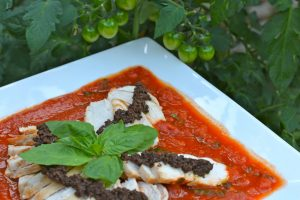 A platter of Chicken with Tapenade and Tomato Basil Sauce garnished with fresh basil.