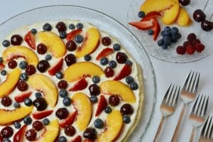 Glazed Fresh Fruit Pizza topped with sliced peaches, cherries, strawberries, raspberries and blueberries.