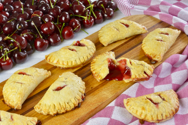 A wooden board covered in Cherry Hand Pies surrounded by an red and white checked tea towel.