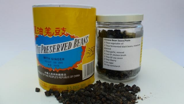 A container of Chinese black beans, also called preserved beans.