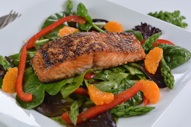 Sesame Salmon on Greens with red pepper, asparagus and orange segments.
