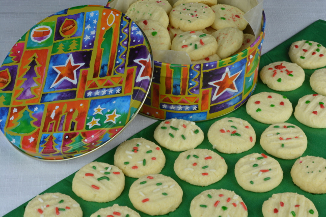 A tin of gluten free Whipped Shortbread decorated with red and green sprinkles.